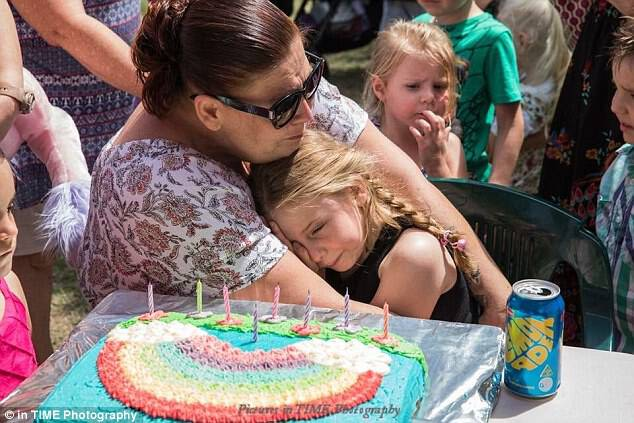 Mia McKay, eight, broke down into happy tears in her mum Sarah's arms when more than 150 people in her Gold Coast community threw her a surprise birthday party