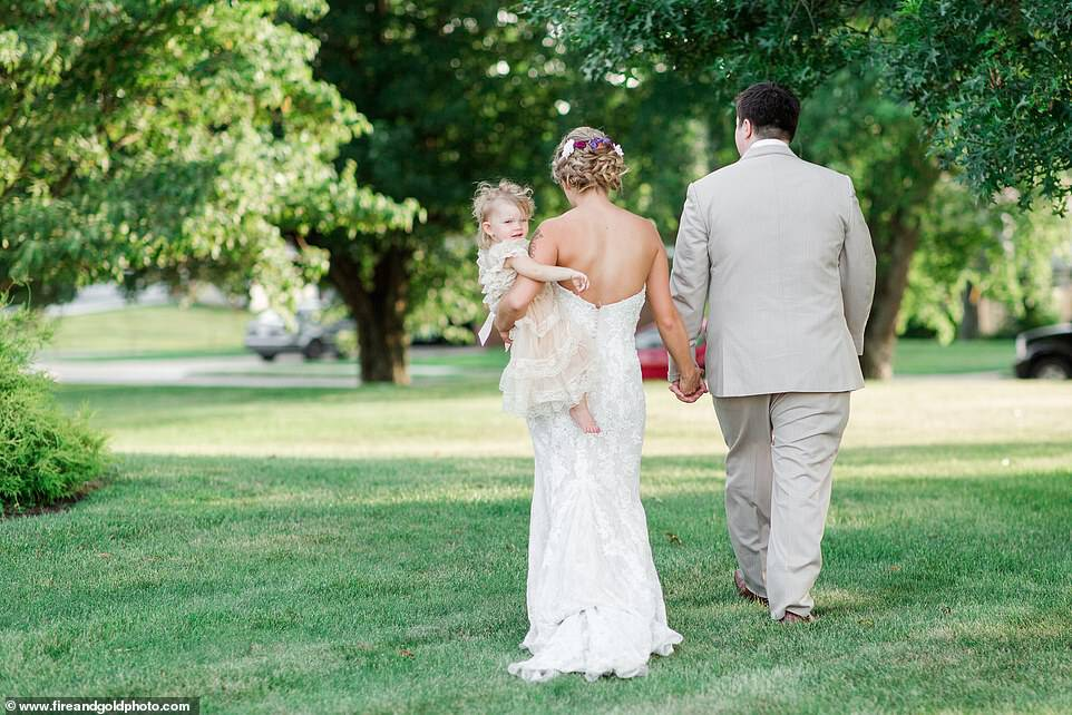 Happily ever after: After Dalton and Jimmy Joe's wedding ceremony, the bride removed the wrap an held the toddler in her arm, revealing that she was wearing an adorable ivory-colored lace gown that the toddler wore for the wedding