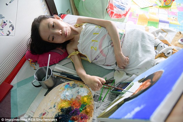 Zhang carefully mixes and places her oil colours on a painting that she's working on