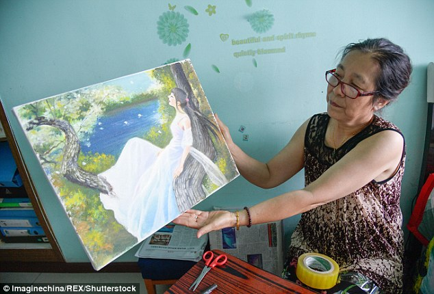 Zhang's mother shows off one of her daughter's masterpiece in Taiyuan city, Shanxi province